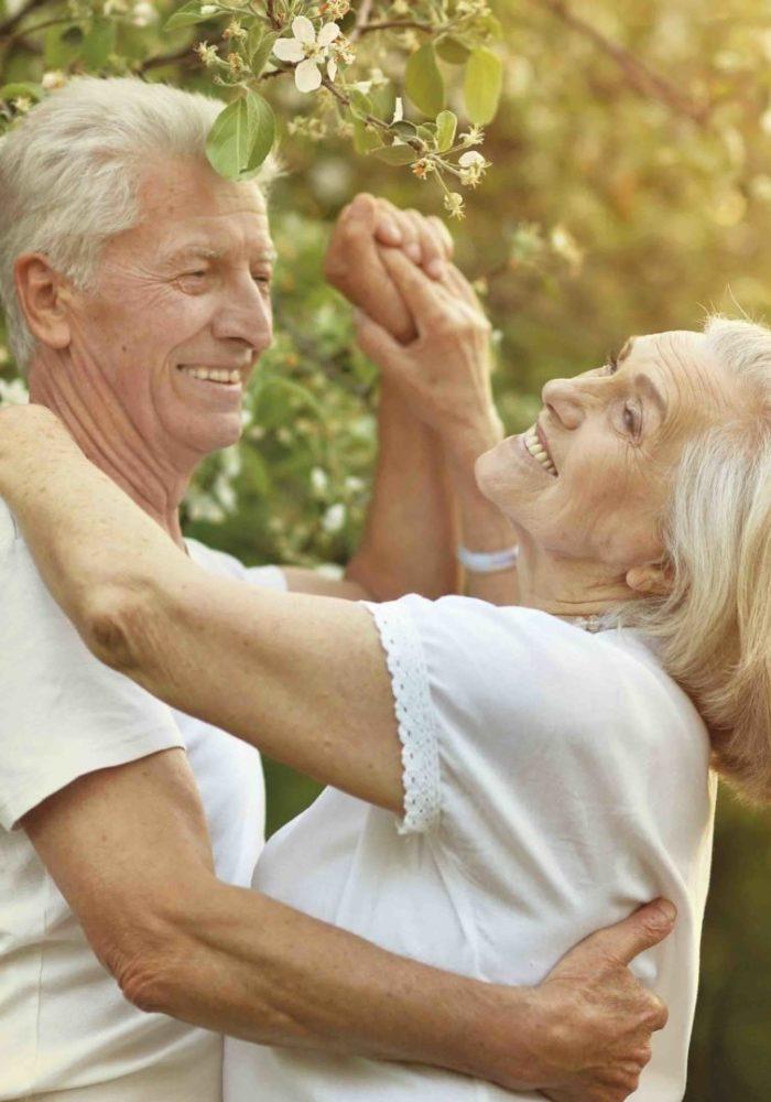 beautiful senior couple dancing near blooming apple tree